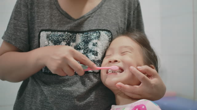mother is brushing her daughter's teeth - brushing stock videos & royalty-free footage