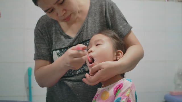 mother is brushing her daughter's teeth - toothpaste stock videos and b-roll footage