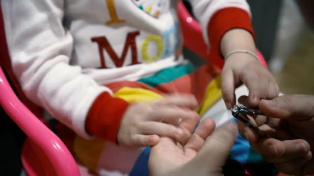 母は彼女の赤ちゃんのための爪を切っています。 - 2歳から3歳点の映像素材/bロール