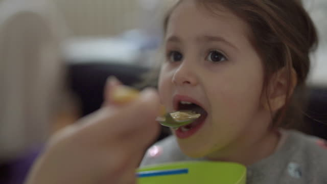 vídeos de stock e filmes b-roll de mother is feeding her 3 year old girl with soup - alimentar