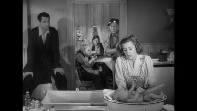 1941 Mother (Irene Dunne) is flustered when trying to bathe the baby with Father (Cary Grant) and others watching