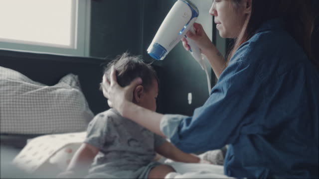 mother is hair drying her baby's hair after a bath - blow drying hair stock videos and b-roll footage