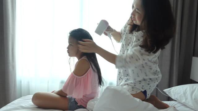vidéos et rushes de la mère est le cheveu séchant ses cheveux de fille après un bain - coiffeur