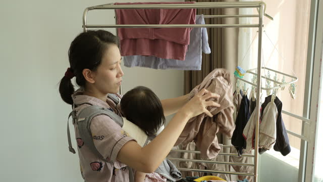 mother is hanging dry the clothes - east asian ethnicity stock videos & royalty-free footage