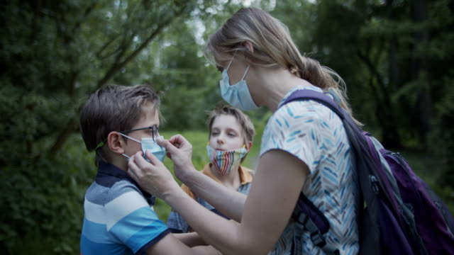 mother is helping children to adjust masks in park during covid-19 pandemic - adjusting stock videos & royalty-free footage
