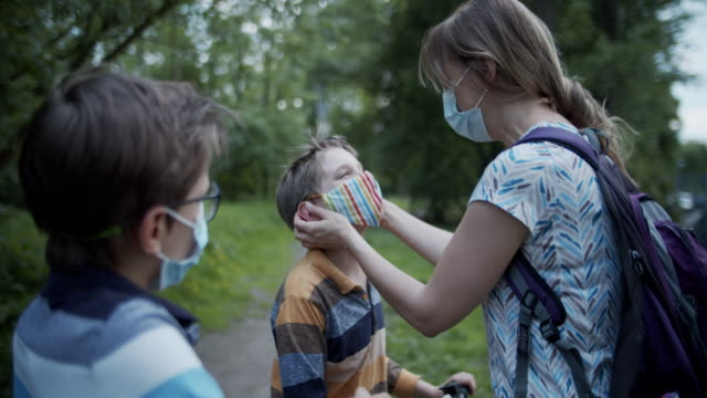 mother is helping children to adjust masks in park during covid-19 pandemic - surgical mask stock videos & royalty-free footage