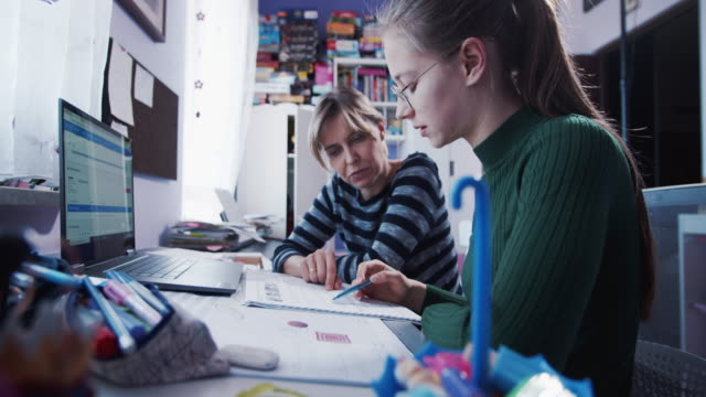 mother is helping daughter with homework in her room. - trainer stock videos & royalty-free footage