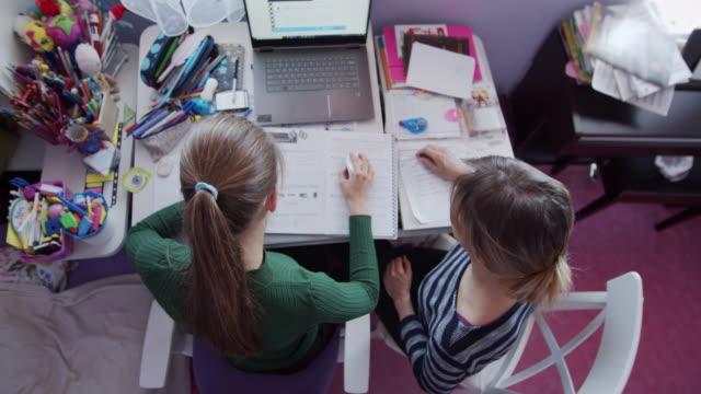 stockvideo's en b-roll-footage met de moeder helpt dochter met thuiswerk in haar ruimte. - e learning