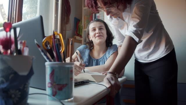 mutter hilft ihrer tochter bei den hausaufgaben zu hause - akademisches lernen stock-videos und b-roll-filmmaterial