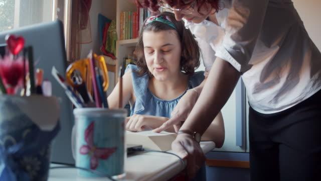 mutter hilft ihrer tochter bei den hausaufgaben zu hause - lernen stock-videos und b-roll-filmmaterial