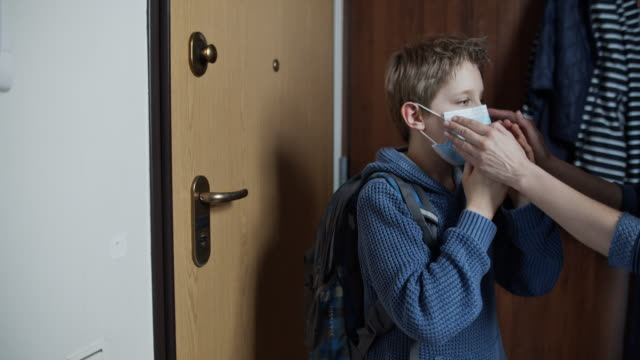 mother is helping son to put on face mask - riapertura delle scuole video stock e b–roll