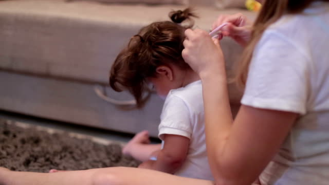 Mother is making pony tail on her baby's hair, while baby is using the phone