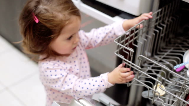 mother is picking up baby bottle and dishes while her baby girl is watching - chores stock videos & royalty-free footage