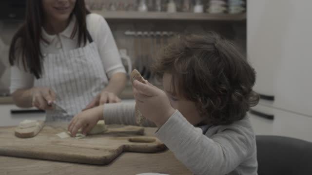 vidéos et rushes de mère prépare le petit déjeuner pour son enfant - petit déjeuner