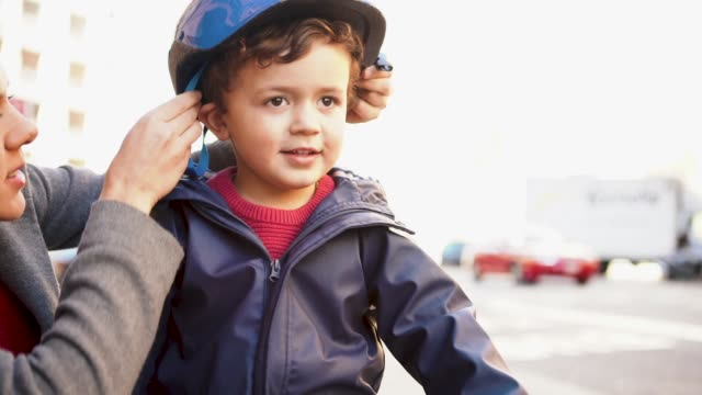 mother is putting safety helmet on his little son's head - protezione video stock e b–roll