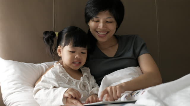 Mother is reading a book with her daughter