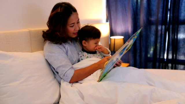 Mother is reading a book with her son