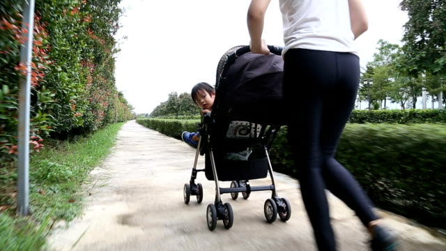 mother jogging with baby boy in stroller. - pushchair stock videos and b-roll footage