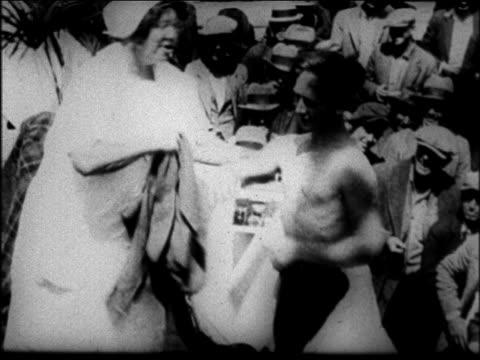 mother jordan helping man take off shirt put on new one at soup kitchen - 1931年点の映像素材/bロール