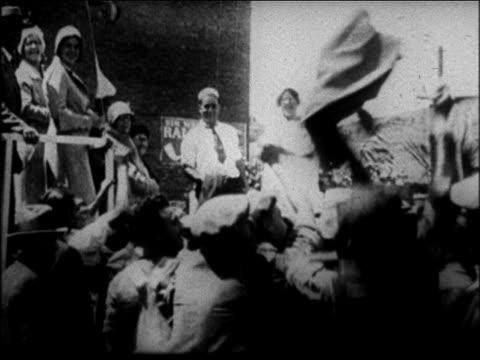mother jordan throwing clothing to crowd of men outdoors / san francisco - 1931年点の映像素材/bロール