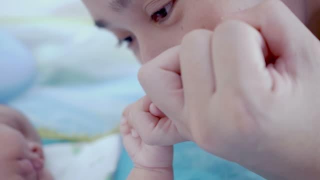 Mother kisses babies finger