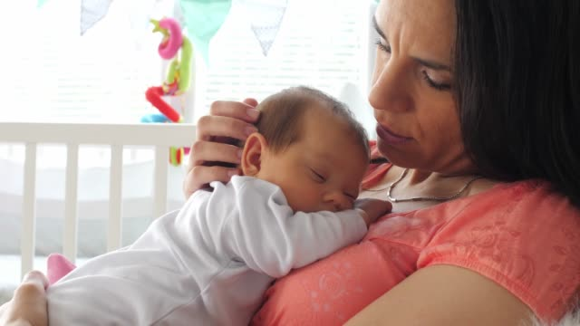 mother kissing and caressing her newborn baby while putting her down for a nap - chest kissing stock videos & royalty-free footage