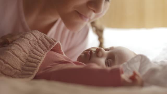 stockvideo's en b-roll-footage met moeder zoenen en die betrekking hebben op slapende baby - kussen beddengoed