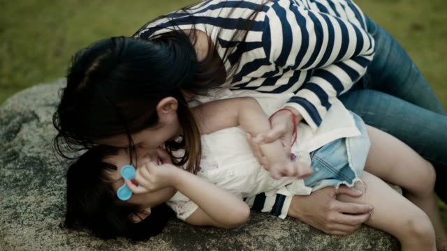 mother kissing daughter in garden - outdoor pursuit stock videos & royalty-free footage
