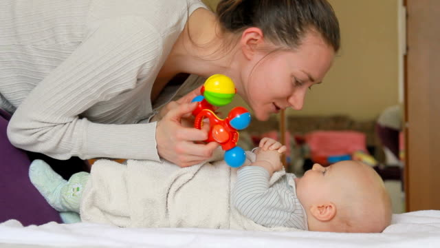 Mother kissing her baby and playing with rattles.