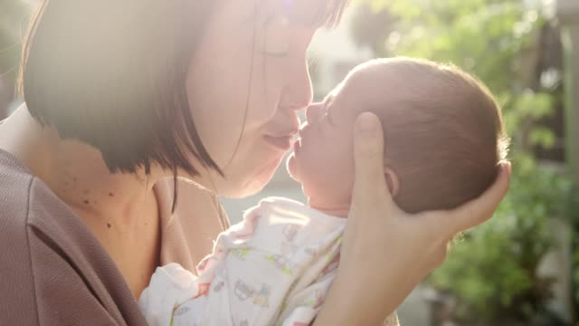 mother kissing her baby boy (0-1 months) at sunset - 0 1 months stock videos & royalty-free footage
