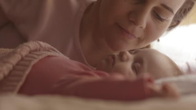 Moeder haar slaperige babymeisje kussen