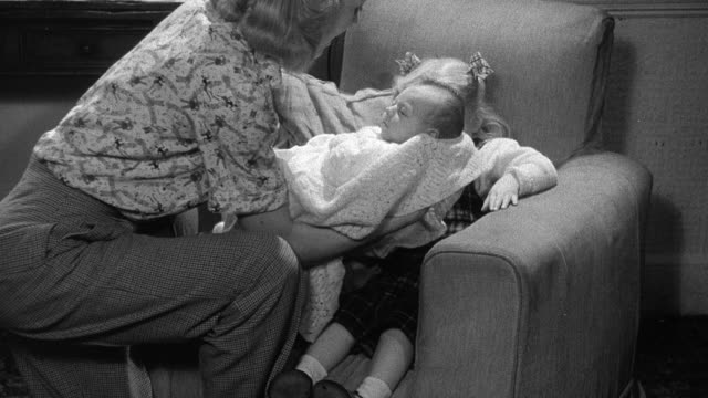 1952 montage mother kneeling by chair and putting baby in her child's lap, child holding baby with mother watching over / wadhurst, england, united kingdom - wadhurst video stock e b–roll
