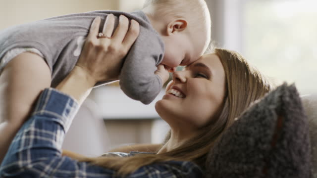 stockvideo's en b-roll-footage met mother laying on sofa kissing and rubbing noses with baby daughter / alpine, utah, united states - eskimokus geven