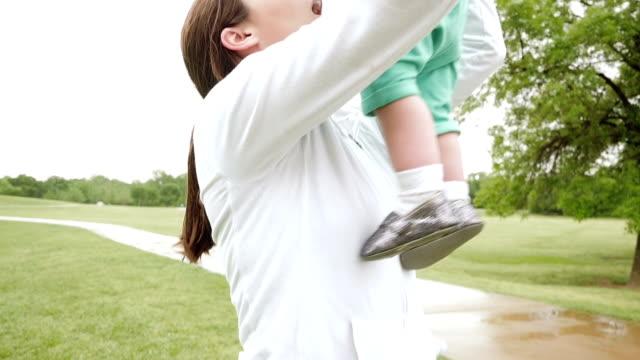 vidéos et rushes de mère et bébé en levant le souffle framboises sur son ventre, leur donnant une étreinte - chatouiller