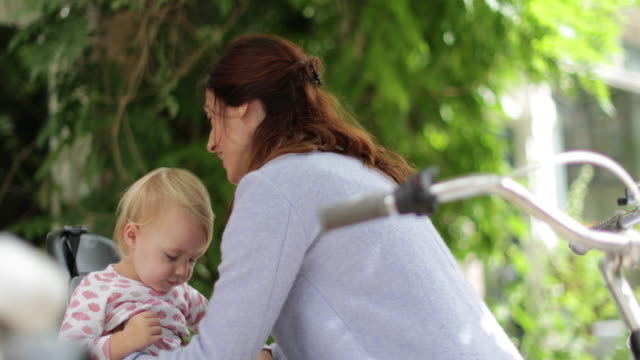mother lifting child into bicycle seat - bicycle seat stock videos & royalty-free footage