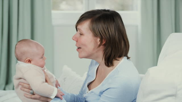 cu mother lifting up baby daughter (2-5 months), smiling and kissing her, brussels, belgium - 2 5 months stock videos & royalty-free footage