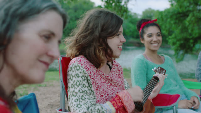 CU. Mother listens and sings along as daughter plays ukulele on camping trip.