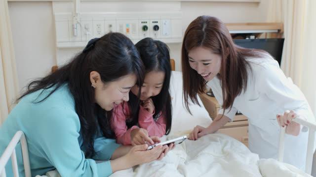 vídeos de stock, filmes e b-roll de matriz, menina e enfermeira pediatra que olham o telemóvel na divisão do hospital das crianças - enfermeira pediátrica