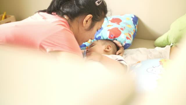 母と彼女の眠っている赤ちゃんにキス - 生後1ヶ月点の映像素材/bロール