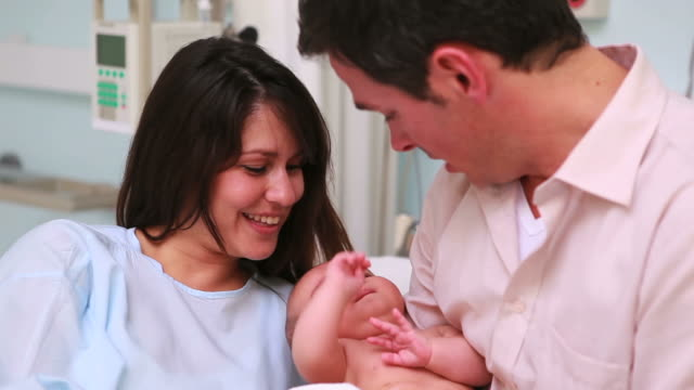 Mother looking at a man holding a new born baby