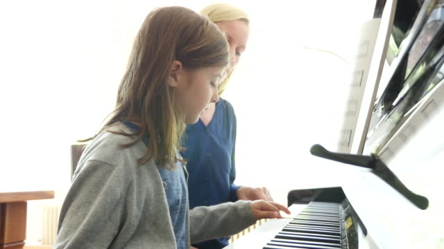 Mother looking at daughter playing piano