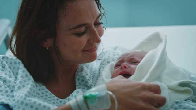 mother looking at infant crying on bed in hospital - unknown gender stock videos & royalty-free footage