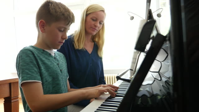 Mother looking at son playing piano at home