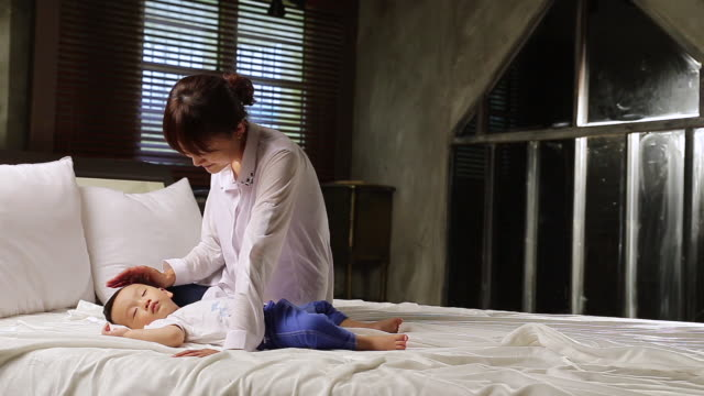 ms mother looking to his sleeping son on bed / jeju, jeju-do, south korea - baby boys stock videos and b-roll footage