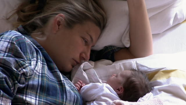 stockvideo's en b-roll-footage met mother lying in bed with newborn daughter watching her sleep - uitgeput