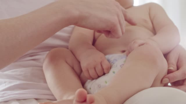 Mother makes massage and stretch for baby stomach