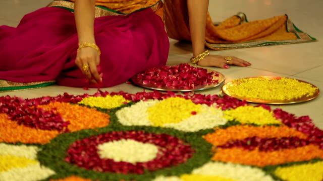 MS TU Mother making rangoli with flower during diwali festival and daughter embracing