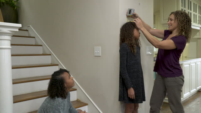 Mother measuring height of youngest daughter.