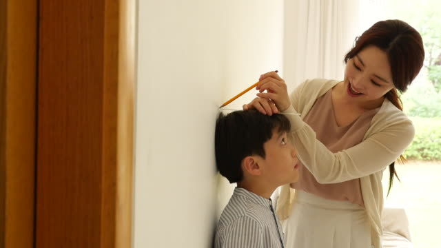 vidéos et rushes de mother measuring son's height in living room - instrument de mesure
