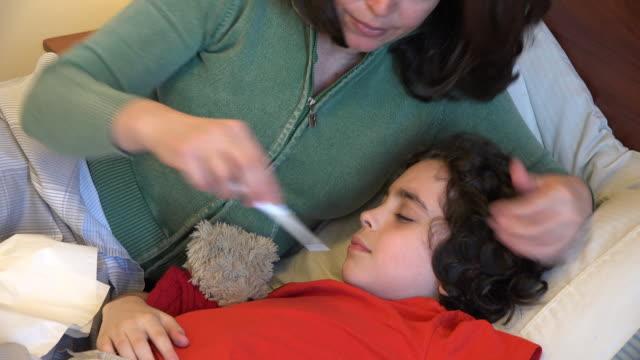 vídeos de stock e filmes b-roll de mother measuring the temperature of her sick child boy - cold temperature
